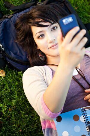 university text: A shot of a mixed race girl texting on the phone at campus