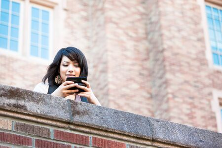 A shot of a mixed race girl texting on the phone at campus photo