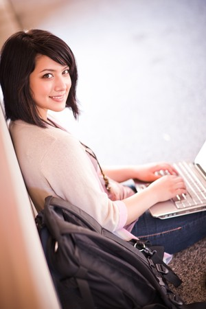 Mixed race college student working on laptop at campus photo