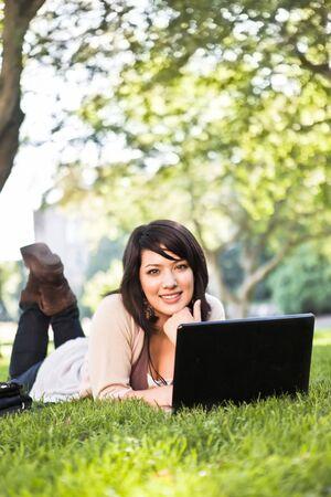 캠퍼스에서 노트북을 작동하는 잔디에 누워 혼합 된 경주 대학 학생