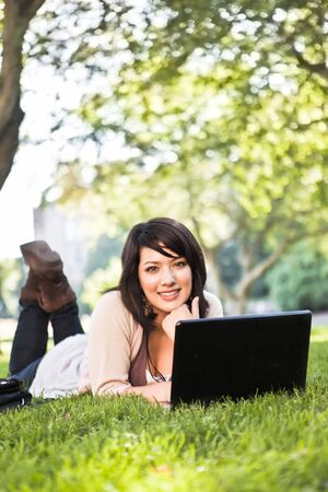 asian american: Mixed race college student lying down on the grass working on laptop at campus