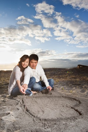 A portrait of an asian couple drawing love symbol on the sand Imagens
