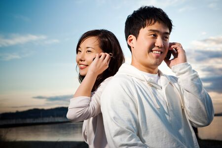A portrait of an asian couple talking on the phone Standard-Bild