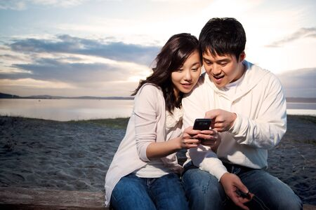 A shot of an asian couple on the phone reading text messages photo