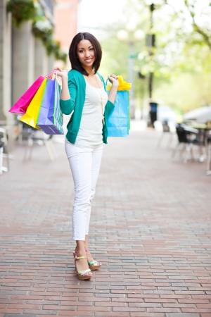 woman shopping bags: A shopping black woman carrying shopping bags outdoor