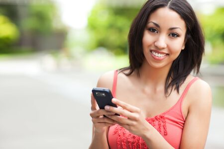 A shot of a mixed race woman texting on her cell phone Stock Photo - 7720102