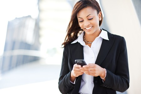cell phone: A shot of a beautiful black businesswoman texting