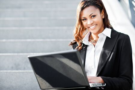A shot of a beautiful black businesswoman working on her laptop outdoor Stock Photo