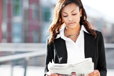 Schuß von schönen schwarzen Kauffrau lesen Zeitung outdoor