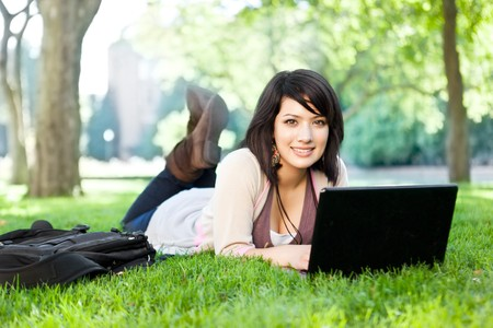 Mixed race college student lying down on the grass working on laptop at campus photo