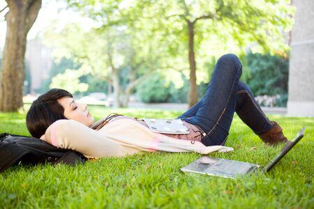 mixed race: Estudiante universitario de raza mixta durmiendo en la hierba en campus