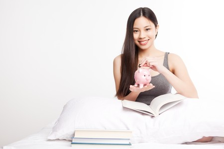 finance girl: A shot of a beautiful asian college student reading on her bed