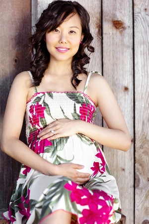 A portrait of a pregnant asian woman outdoor
