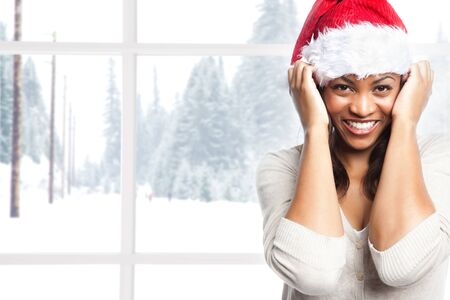 A shot of a black woman celebrating christmas wearing santa hat photo