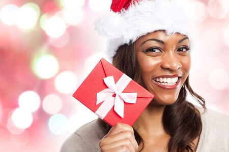 A black woman celebrating christmas holding a gift box photo