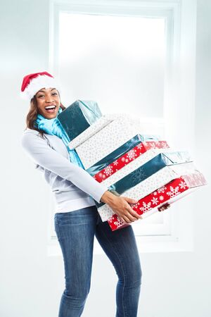 happy christmas: A black woman celebrating christmas carrying gift boxes Stock Photo