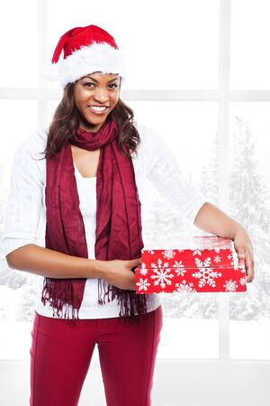 An isolated shot of a black woman celebrating christmas carrying gift boxes photo