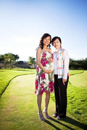 A portrait of a pregnant asian woman with her mother outdoor photo