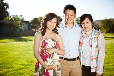 彼女の夫と彼女の母親を屋外で妊娠中のアジアの女性の肖像画