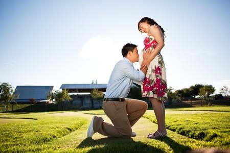 mujer arrodillada: Un retrato de una mujer embarazada con su esposo besando a su vientre
