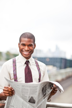 A portrait of a smiling black businessman reading newspaper outdoor Stock Photo - 7893672