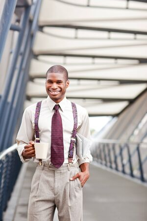 A smiling black businessman holding a coffee cup and newspaper outdoor Stock Photo - 7893680
