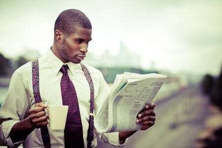 A portrait of a black businessman reading newspaper outdoor