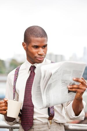 A portrait of a smiling black businessman reading newspaper outdoor Stock Photo - 7893681