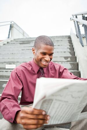 A portrait of a smiling black businessman reading newspaper outdoor photo