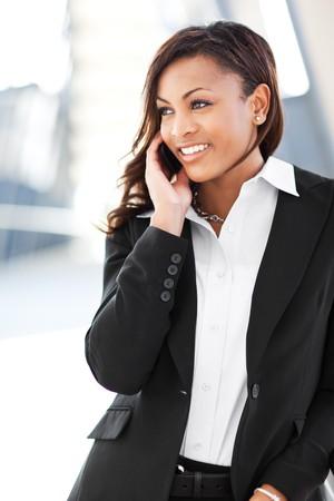 Een schot van een mooie zwarte zaken vrouw op de telefoon