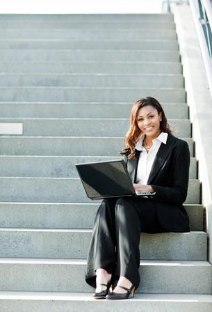 그녀의 노트북 야외에서 작업하는 아름 다운 검은 사업가의 총