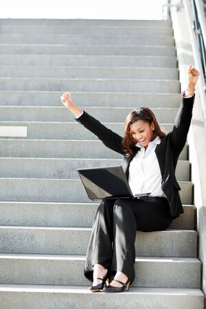 excited business woman: A shot of a beautiful black businesswoman working on her laptop outdoor Stock Photo