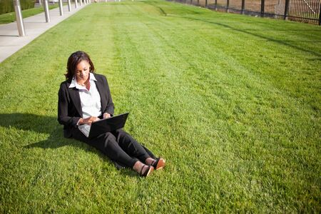 white work: A shot of a beautiful black businesswoman working on her laptop outdoor Stock Photo