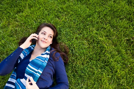 lying in grass: Un disparo de un estudiante de raza mixta, hablando por tel�fono