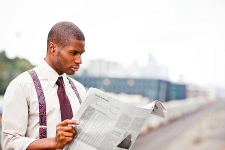 black business men: A portrait of a black businessman reading newspaper outdoor