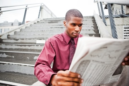 A portrait of a black businessman reading newspaper outdoor photo