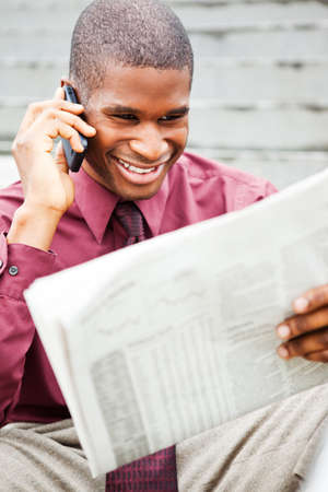 A portrait of a smiling black businessman reading newspaper outdoor Stock Photo - 8066314