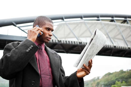 A portrait of a black businessman reading newspaper outdoor Stock Photo - 8066326