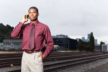 black and white railroad tracks: A shot of a black businessman on the phone Stock Photo