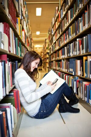 university text: A portrait of a mixed race college student texting at library Stock Photo