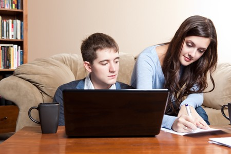 paying: A couple paying bills by using online banking at home