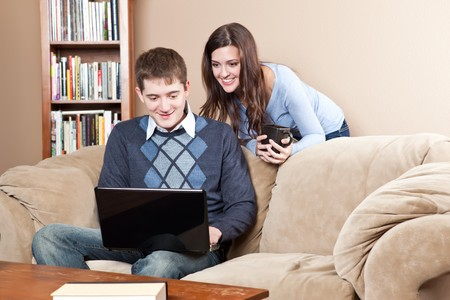 A shot of a young couple working on laptop at home photo