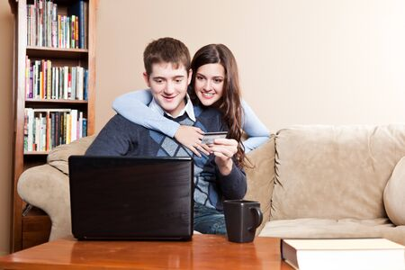 A happy couple holding a credit card shopping online Stock Photo - 8135775
