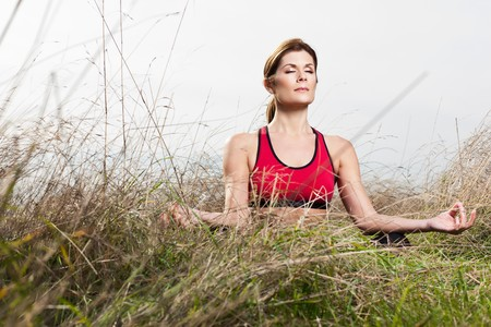 A beautiful caucasian woman doing yoga meditation outdoor in a park Imagens