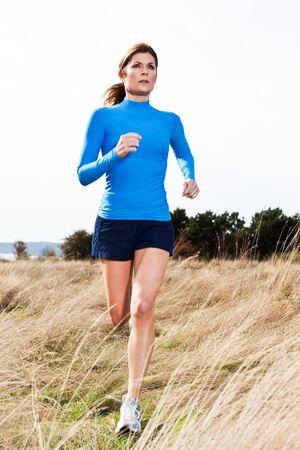 mujeres corriendo: Una mujer activa y cauc�sicos hermosa que se ejecutan al aire libre en un parque