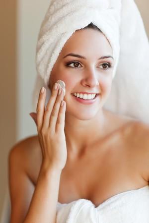 彼女の顔にローションを適用する若い美しい女性のショット 写真素材