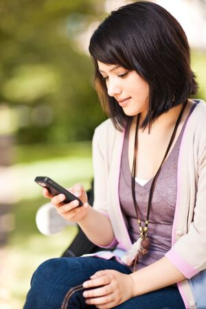 sms text: A shot of a mixed race girl texting on the phone at campus