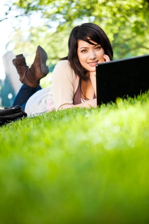 Mixed race college student lying down on the grass working on laptop at campus