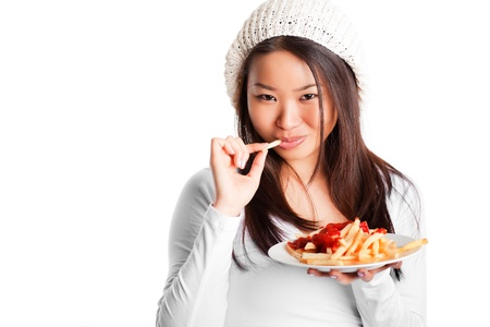 An isolated shot of an asian girl eating french fries