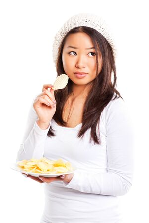 An isolated shot of an asian girl eating potato chips